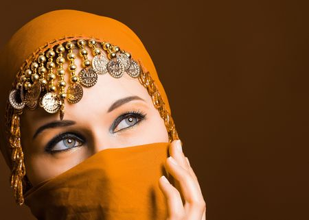 eyes hidden: a beautiful woman wearing a red exotic veil