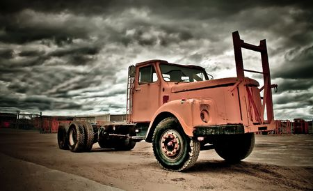 old and weathered truck in front of dark sky photo