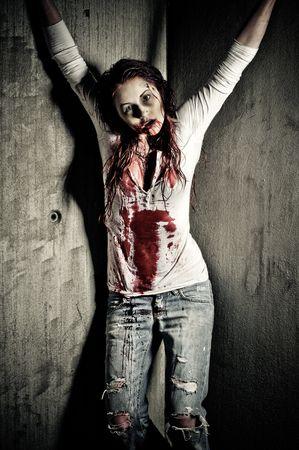 sangre derramada: una chica de zombie aspecto sangriento y miedo  Foto de archivo