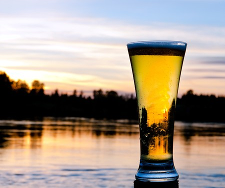 setting sun: a refreshing beer in front of a scandinavian sunset Stock Photo