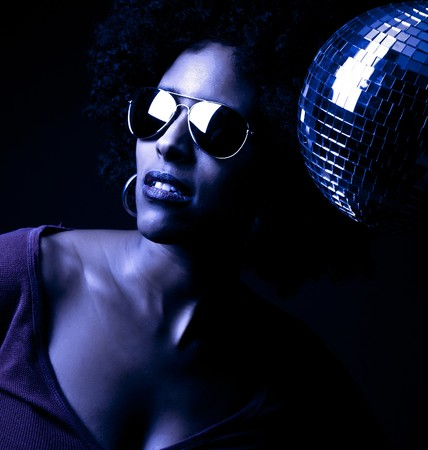 a 70s style disco girl with a mirror ball Stock Photo
