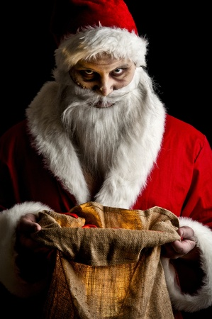 evil: a scary looking santa holding  a glowing present bag
