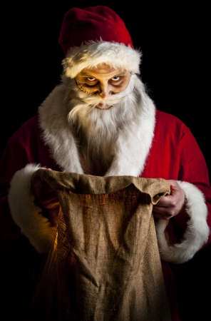 a scary looking santa holding  a glowing present bag photo