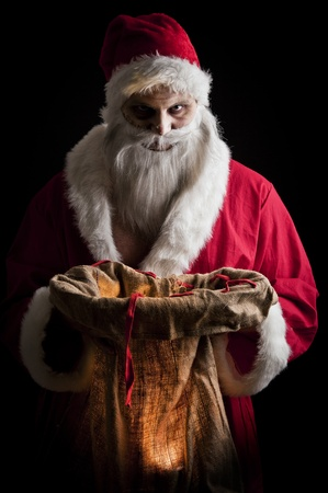 a scary looking santa holding  a glowing present bag Stock Photo - 8381395