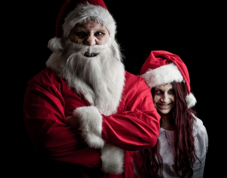 portrait of a scary looking santa claus and an elf photo