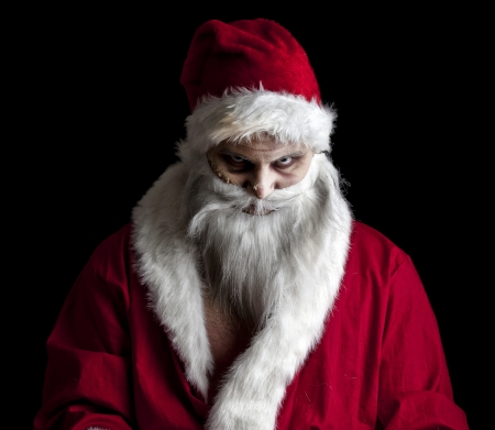 a scary looking santa holding  a glowing present bag Stock Photo - 8462644