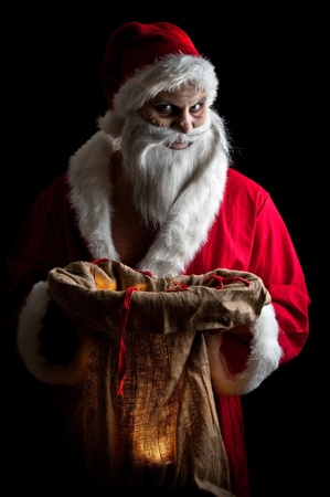 a scary looking santa holding  a glowing present bag Stock Photo - 8462651