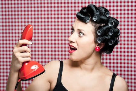 a 50s style housewife with hair rolls gossiping in a red vintage phone Stock Photo - 8734398