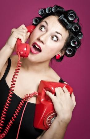 ama de casa: ama de casa de estilo de un de los a�os 50 con rollos de pelo charlando en un tel�fono rojo de vintage Foto de archivo