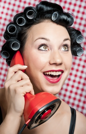 a 50s style housewife with hair rolls gossiping in a red vintage phone Stock Photo - 8736949
