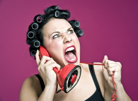 a 50s style housewife with hair rolls gossiping in a red vintage phone Stock Photo - 8736938
