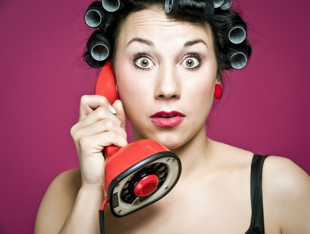 a 50s style housewife with hair rolls gossiping in a red vintage phone photo