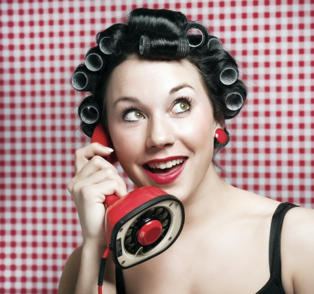 a 50s style housewife with hair rolls gossiping in a red vintage phone Stock Photo - 8738444
