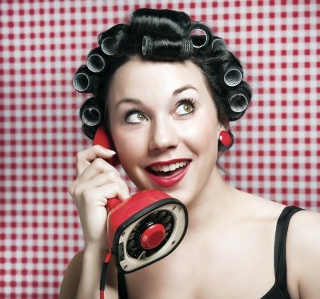 gossip: een 50s stijl huis vrouw met haar rollen roddelen in een rode vintage telefoon