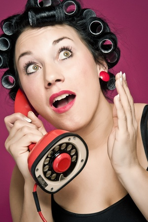 a 50s style housewife with hair rolls gossiping in a red vintage phone Stock Photo - 8738446