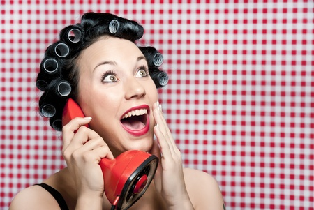 rumours: a 50s style housewife with hair rolls gossiping in a red vintage phone