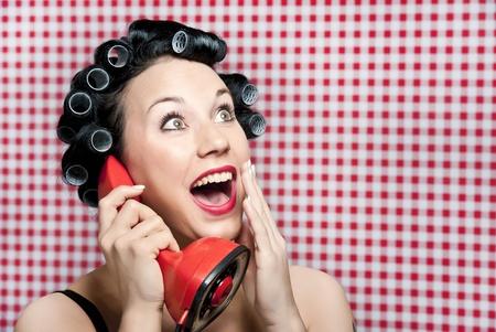 gossip: een 50s stijl huisvrouw met haar rollen roddelen in een rode vintage telefoon