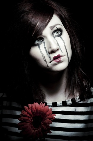 a sad female mime clown with a red flower Stock Photo - 8945642
