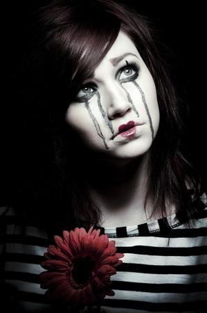 pantomime: un payaso triste mime femenina con una flor roja
