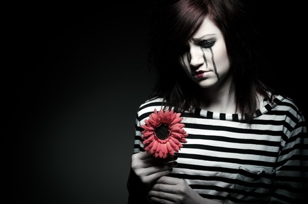 a sad female mime clown with a red flower photo