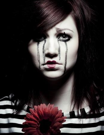 clowngesicht: traurig weiblich Mime Clown mit eine rote Blume