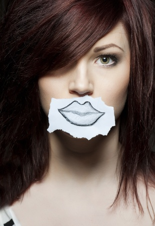 a young beauty with a drawn paper mouth Stock Photo - 9010448
