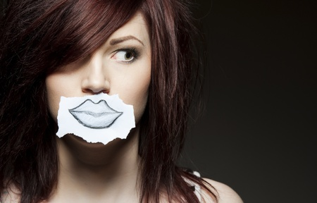 a young beauty with a drawn paper mouth Stock Photo - 9010524
