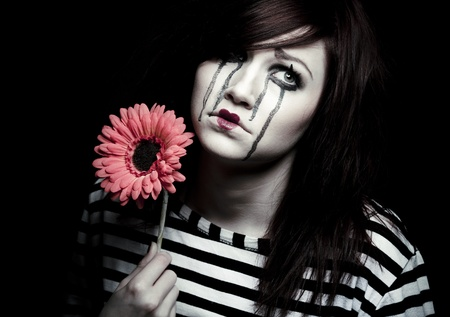 a sad female mime clown with a red flower Stock Photo