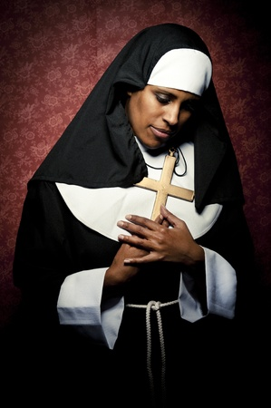 an african nun holding a metal cross photo
