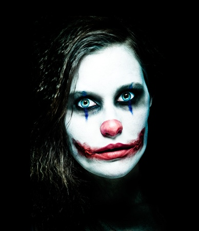 evil clown: a scary female clown staring from the dark