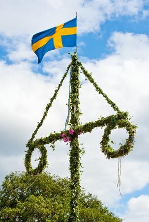 Un poste tradicional de mediados del verano sueco con una bandera sueca Foto de archivo - 9986049