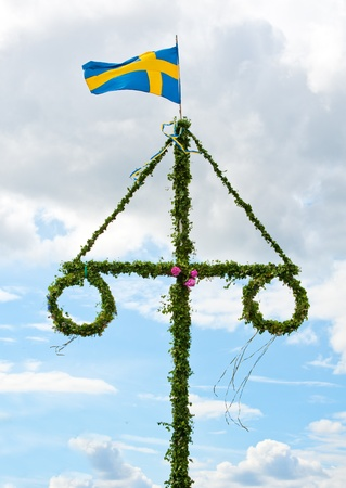 midsummer pole: a traditional swedish midsummer pole with a swedish flag