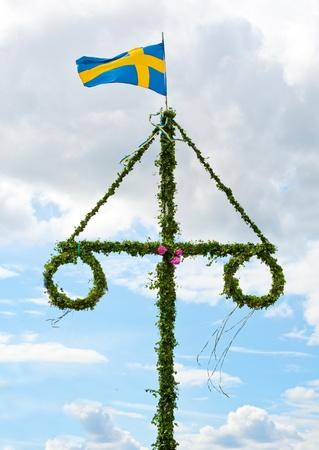 Un polo de verano sueco tradicional con una bandera sueca Foto de archivo - 9986095