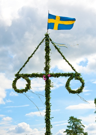 a traditional swedish midsummer pole with a swedish flag
