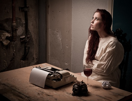 female prisoner: a mad girl wearing a straight jacket in front of a typewriter