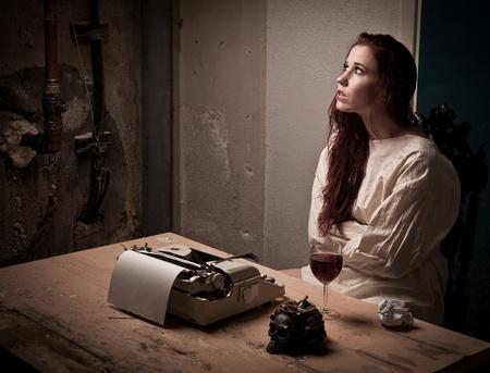 gefangener: ein mad Mädchen tragen eine Zwangsjacke an einer Schreibmaschine