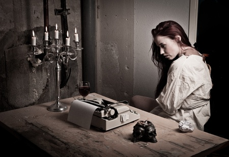 a mad girl wearing a straight jacket in front of a typewriter