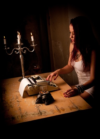 lonely person: a young woman is writing on a typewriter