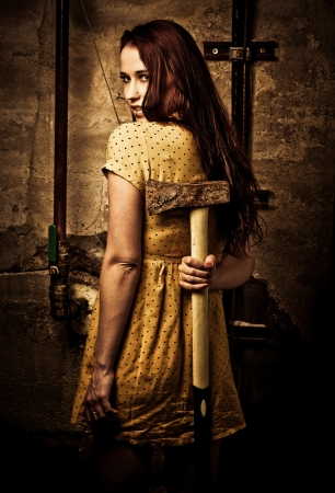 axe: a young redhaired woman with a rusty axe Stock Photo