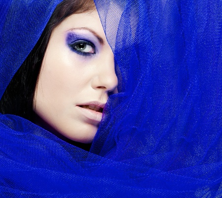face shot of a beautiful brunette with purple make up and a colorful veil photo