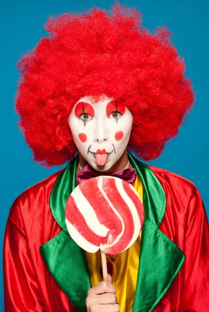 a female clown with colorful clothes and makeup holding a lolipop