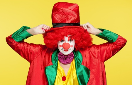 a female clown with colorful clothes and makeup