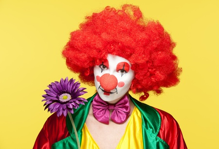 a female clown with colorful clothes and makeup holding a flower photo