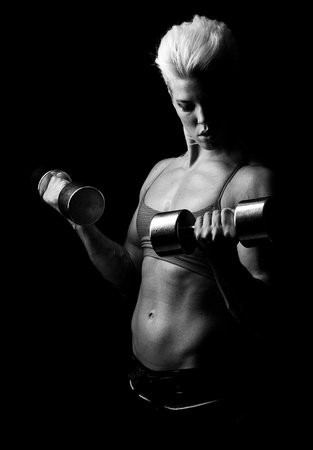 a young muscular fitness girl striking a pose with dumbells