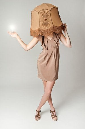 lampshade: a fashion portrait of a european brunette wearing a retro lampshade and holding a glowing lightbulb