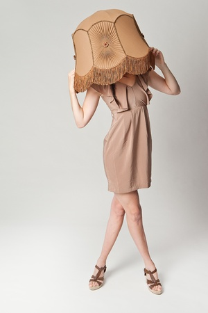 lampshade: a high fashion portrait of a european brunette wearing a retro lampshade