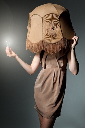 a fashion portrait of a european brunette wearing a retro lampshade and holding a glowing lightbulb photo