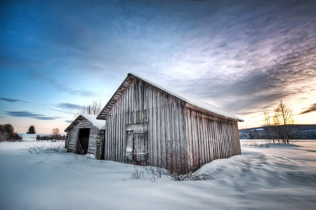 an old weathered barn in a winter landscape photo