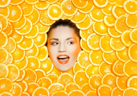 a creative beauty shot with oranges and matching makeup