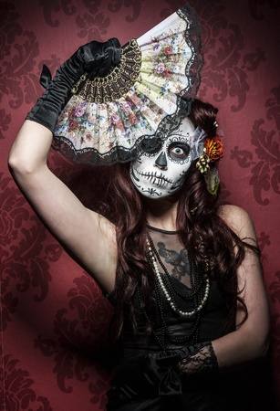 faceart: a woman with her face painted as a traditional day of the dead sugarskull mask Stock Photo